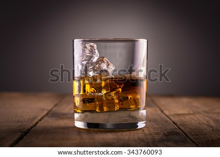 Glass of whiskey, classy, with ice, on wooden table - stock photo