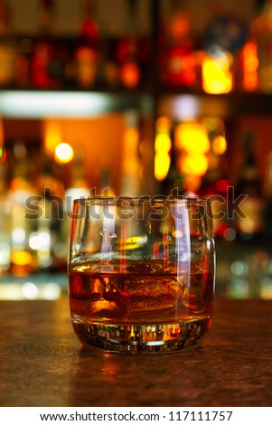 glass of whiskey on a wooden table bar on the background of bright lights of the bar - stock photo