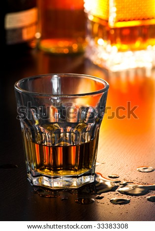 Glass of whiskey on table with drops, shallow DOF - stock photo