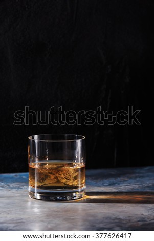 Glass of whiskey on the rocks on the table. Concept of hard liquor. Vertical - stock photo