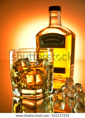 Glass of whiskey on the rocks with a bottle in the background - stock photo