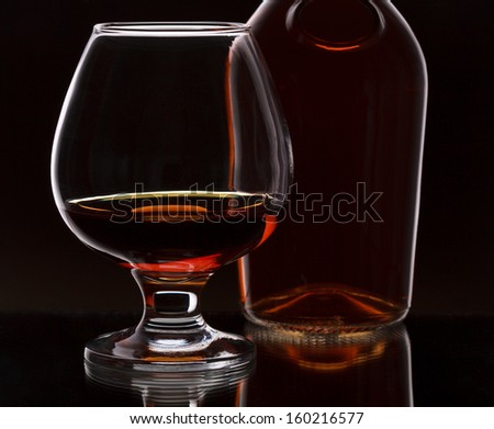 Glass of whiskey with bottle, on dark background, selective focus on the glass  - stock photo