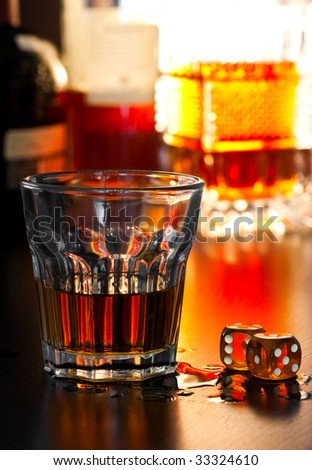 Glass of whiskey with dice, shallow DOF - stock photo