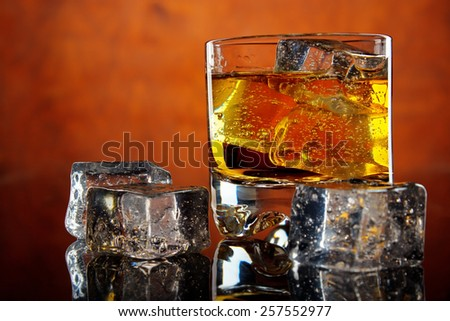 Glass of whiskey with ice cubes on dark reflective table , red background - stock photo