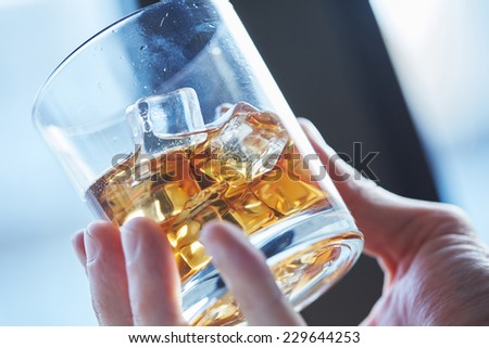 glass of whiskey with ice in his hand  - stock photo