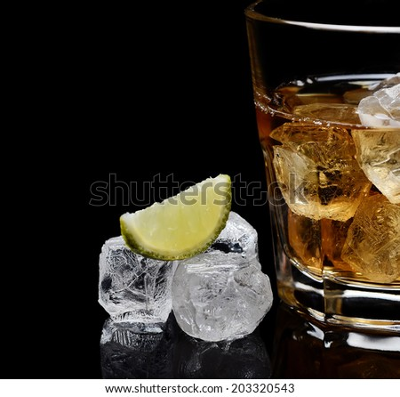 glass of whiskey with ice on a black background - stock photo