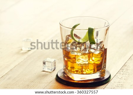 Glass of whiskey with ice on wooden background, warm color tone - stock photo