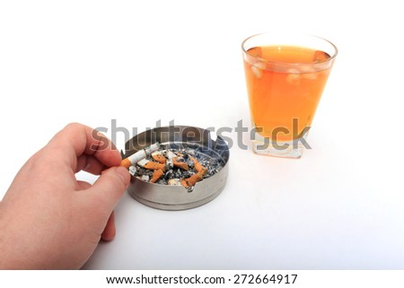 Glass of whiskey with ice. With an ashtray and a cigarette on a white background. - stock photo