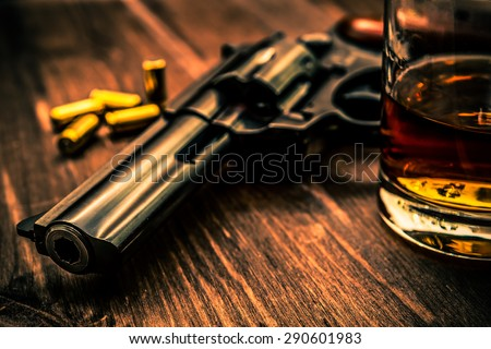 Glass of whiskey with revolver on the wooden table. Close up view, focus on the barrel of revolver, image vignetting and the orange-blue toning - stock photo