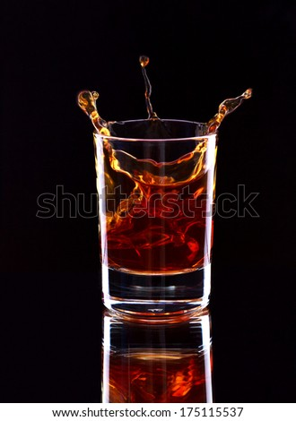 Glass of whiskey with splash on dark background, selective focus on the glass - stock photo