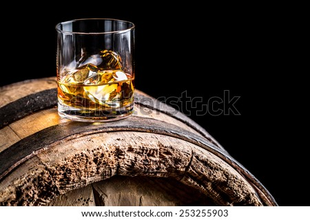 Glass of whisky with ice on old wooden barrel - stock photo