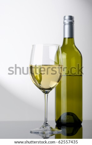 Glass of White Wine, A single glass of white wine, with a green bottle in the background - stock photo