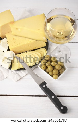 Glass of white wine and assorted cheese with olives on rustic wooden table. - stock photo