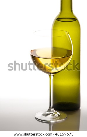 Glass of white wine and bottle in back light on light background. - stock photo