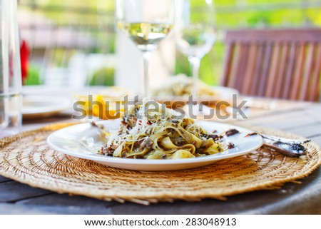 Glass of white wine and dish with pasta - stock photo