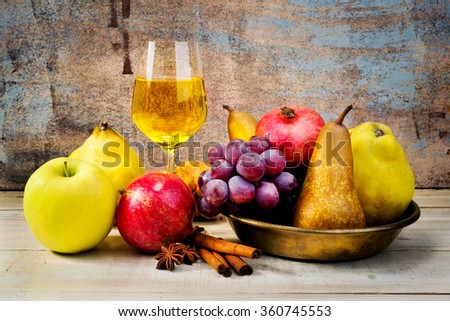 glass of white wine and fruit in copper tray on wooden table - stock photo