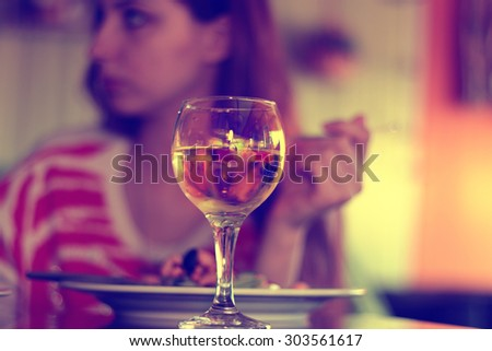 glass of white wine in a restaurant on a background of a person - stock photo