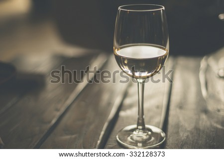 Glass of White Wine on The Wooden Table - stock photo