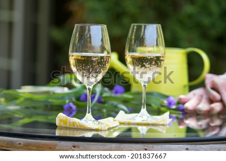 Glass of white wine set outdoors on glass table with flowers and other greenery, as well as a watering can and gardening gloves for a break from gardening - stock photo