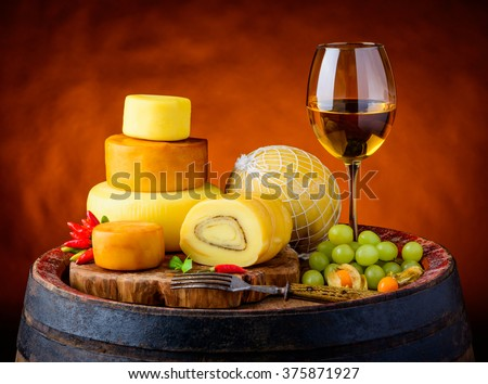 Glass of white wine with cheese wheele, smoked cheese and truckle cheese in vintage still life - stock photo
