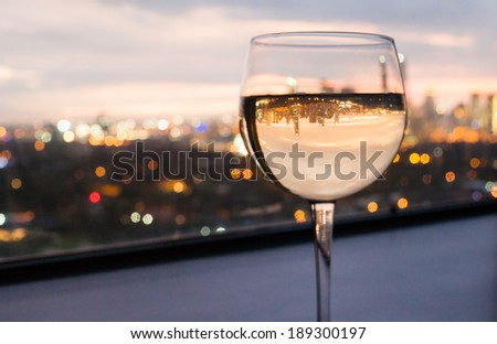 Glass of white wine with city view. - stock photo