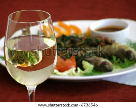 Glass of white wine with fried fish on background - stock photo
