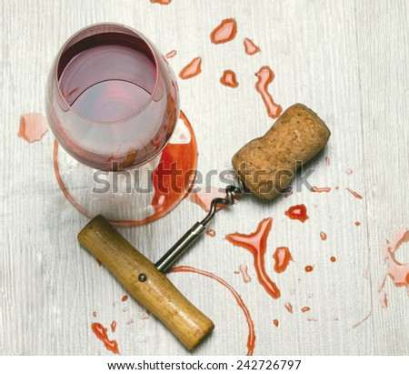 glass of wine and a corkscrew with cork wood surface with stains from wine.toned - stock photo