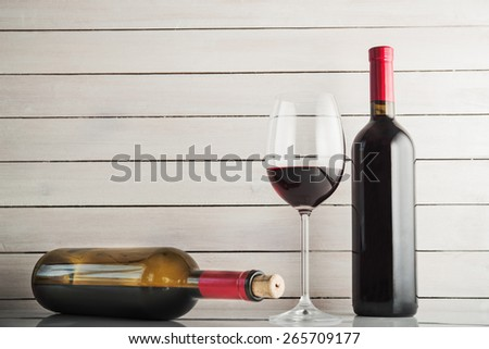 Glass of wine and bottle on white wood background - stock photo