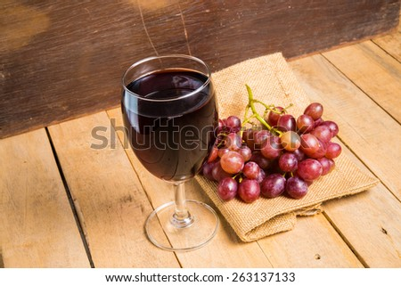 glass of wine and grapes on wodden background - stock photo