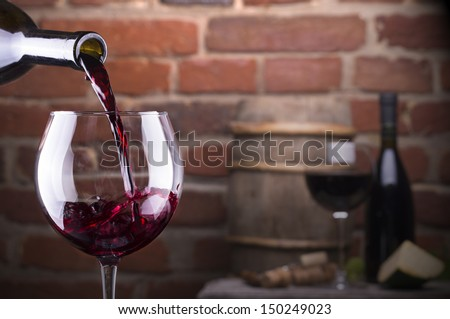 Glass of wine and some fruits, bottle of wine, cheese against a brick wall. - stock photo
