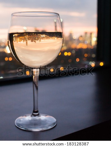 Glass of wine in the restaurant with city view. - stock photo
