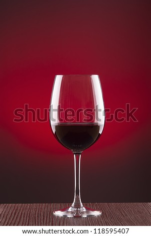 Glass of wine over red background - stock photo