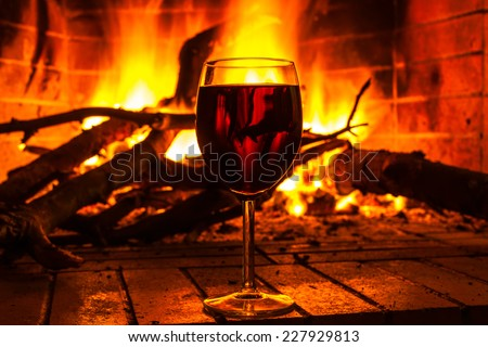 Glass of wine standing by the fireplace on a background of fire flame - stock photo