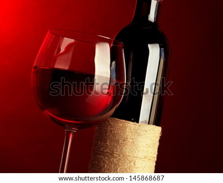 Glass of wine with bottle on bright red background - stock photo