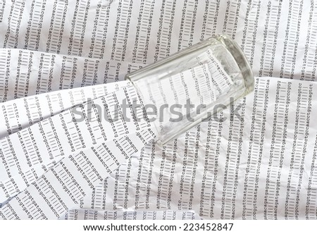 Glass on a background of crumpled DNA sequence with stripes of DNA sequences in it - stock photo