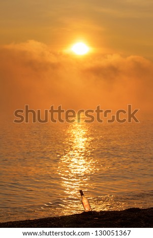 glass on sand with message in the sunrise with fog and clouds - stock photo