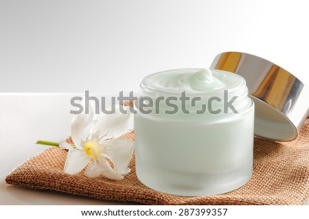 Glass open jar with facial or body cream on burlap. With lid and flower.Isolated background. Front view. - stock photo