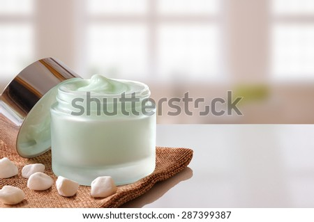 Glass open jar with facial or body cream on burlap. with lid and small stones.Windows background. Front view. - stock photo