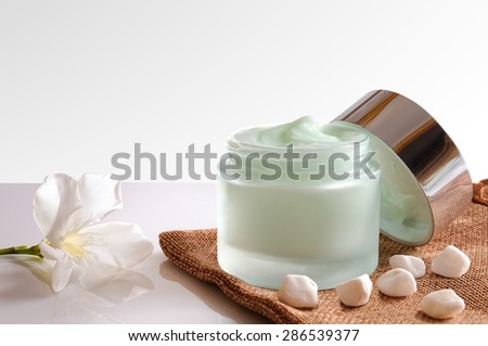Glass open jar with facial or body cream on burlap. with lid, stones and flower. White isolated background. Front view. - stock photo