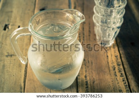 Glass pitcher of water and glass on wooden table background, vintage color tone. - stock photo
