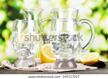Glass pitchers of water and glasses on wooden table on natural background - stock photo