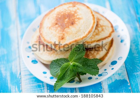 Glass plate with fritters and mint leaves, horizontal shot - stock photo