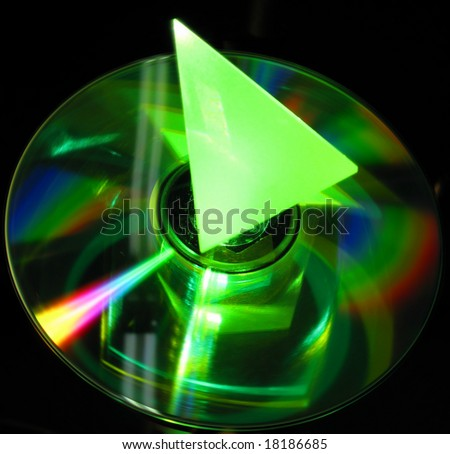 glass prism on CD lit up by green laser beam - stock photo