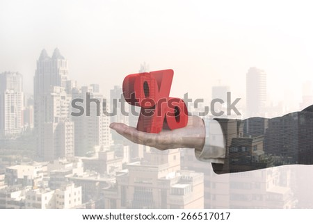 Glass reflection of hand showing 3D red percentage sign with city buildings background - stock photo