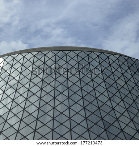Glass rounded modern building against blue sky - stock photo