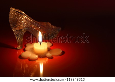 Glass slipper near lighting candle on black and red background with free space for text - stock photo