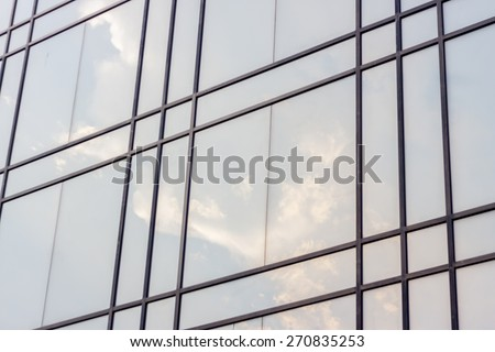 glass surface of contemporary angle of business building - stock photo
