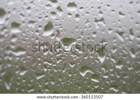 Glass surface with water drops in a rainy day - stock photo