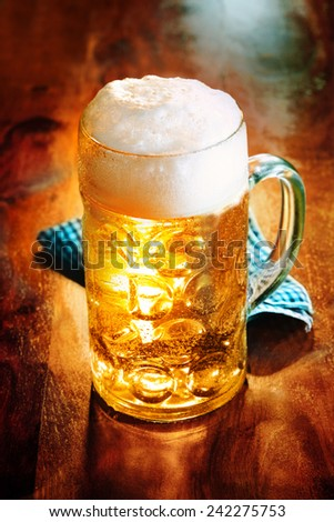 Glass tankard of golden frothy craft beer brewed and distributed locally for its distinctive flavor on a wooden counter in a pub or bar - stock photo