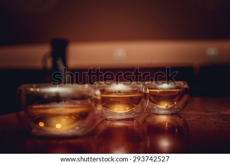 Glass tea cups in a shadow on wood tray. - stock photo